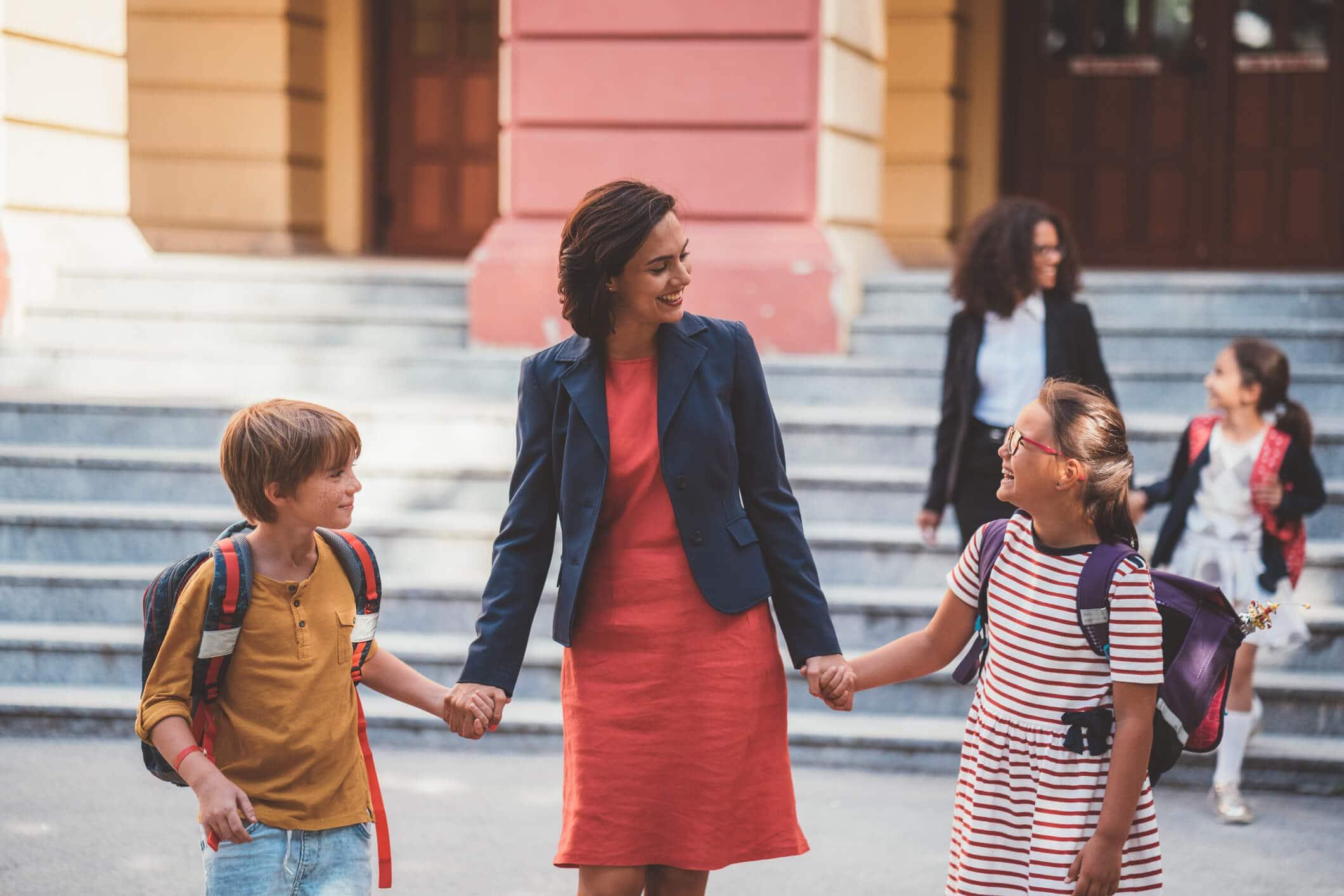 mãe levando filhos para eventos escolares