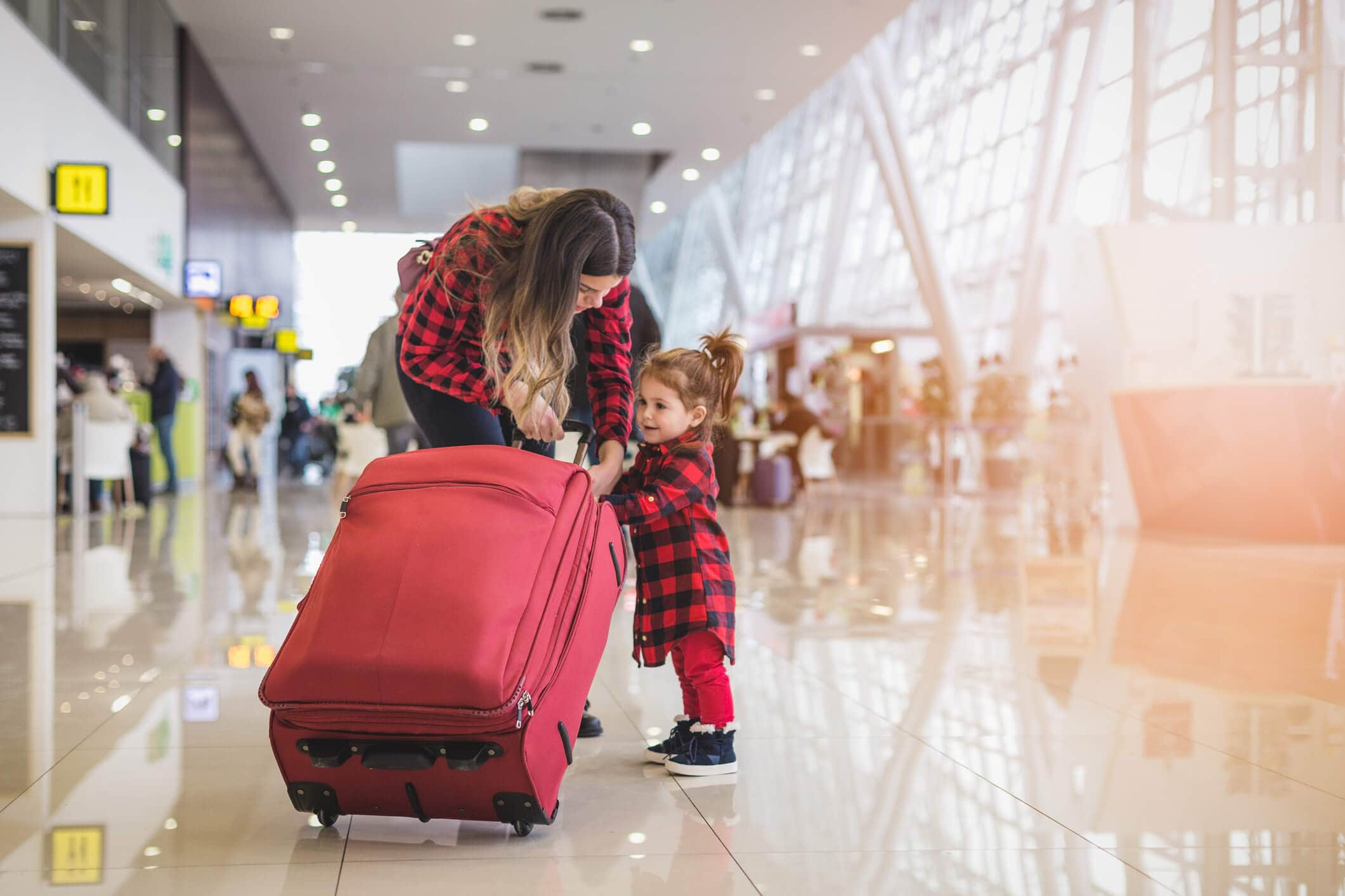 Mulher com uma mala e uma criança no aeroporto verificando o seguro de viagem.