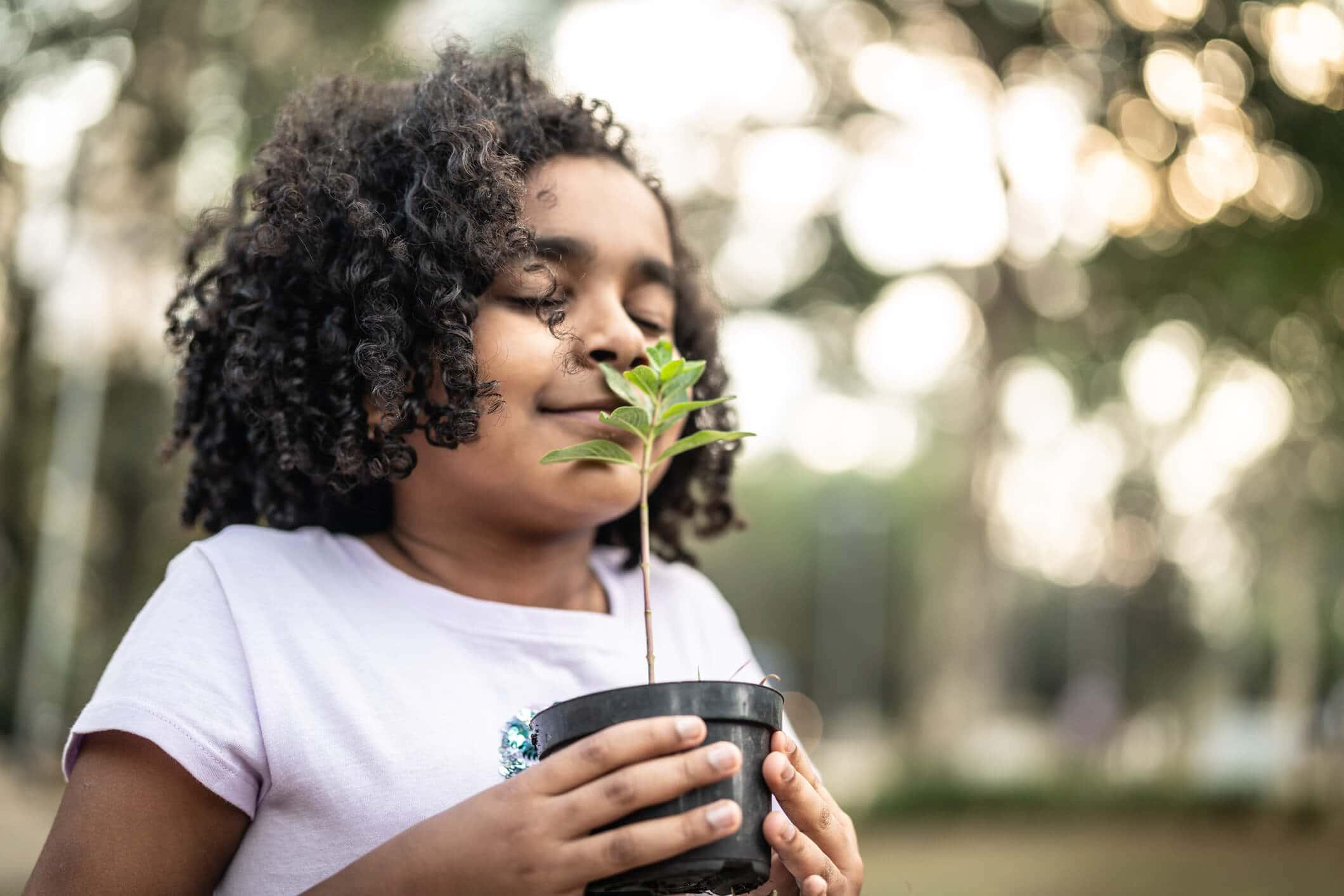 Criança com vaso de plantas na mão representando o tema: educação ambiental para crianças